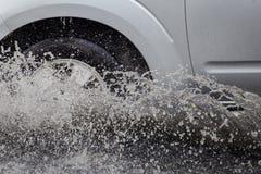 O carro espirra através de uma grande poça em uma rua inundada Foto de Stock Royalty Free