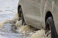 O carro espirra através de uma grande poça no inundada Imagem de Stock