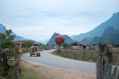 O carro está na estrada com uma montanha e o balão está no fundo fotografia de stock royalty free