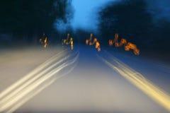 O carro ilumina-se nas ruas na noite e obscuro Imagens de Stock Royalty Free