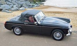 O carro minúsculo preto clássico de MG estacionou no passeio da frente marítima com o mar no fundo Imagens de Stock