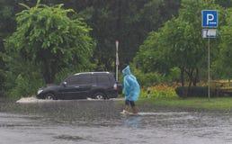 O carro monta na chuva pesada em uma estrada inundada Imagens de Stock Royalty Free
