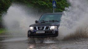 O carro monta na chuva pesada em uma estrada inundada Fotos de Stock Royalty Free