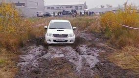 O carro move-se na trilha suja da reunião video estoque