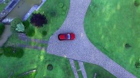 O carro na entrada de automóveis perto da lagoa artificial no vídeo da antena do recurso da vila video estoque