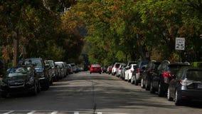 O carro passa casas na rua alinhada árvore da vizinhança filme