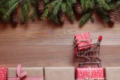 O carro pequeno da compra com um presente em presentes do Natal em um fundo de madeira Fotos de Stock