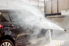 O carro preto de lavagem pela arma da arruela da pressão na lavagem de carros compra Imagem de Stock