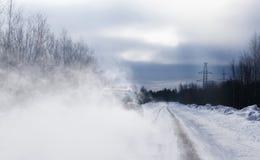 O carro quando alcançar levantar um laço da visibilidade dos pobres da poeira da neve Estrada lisa perigosa foto de stock