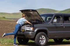 O carro quebra na estrada com a jovem mulher imagem de stock royalty free
