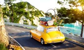 O carro retro pequeno bonito com malas de viagem e bicicleta na parte superior vai pela estrada Foto de Stock