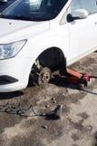 O carro sem roda e levanta acima pela substituição hidráulica, esperando do pneu fotografia de stock