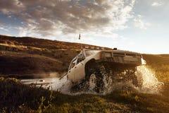 O carro SUV supera a água no fundo offroad Imagens de Stock