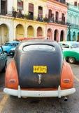O carro velho estacionou perto das construções coloridas em Havana Foto de Stock
