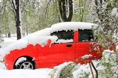 O carro vermelho, coberto com a neve durante um blizzard Fotos de Stock Royalty Free