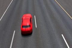 O carro vermelho move-se rapidamente na estrada. imagem de stock