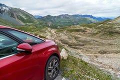 O carro vermelho para viajar está estando na estrada da montanha nos cumes, Áustria Imagens de Stock