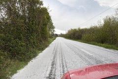 O carro vermelho que viajam através de uma saraiva e a neve atacam Fotos de Stock