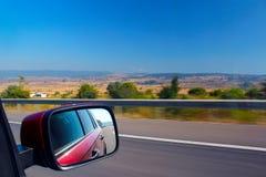 O carro vermelho vai rapidamente na estrada Ideia da paisagem da janela de carro imagem de stock