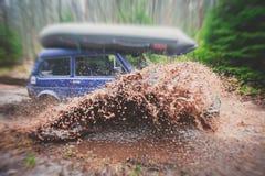 O carro 4wd offroad de Suv monta através da poça enlameada, estrada fora de estrada da trilha, com um respingo grande, durante um Fotos de Stock