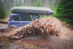 O carro 4wd offroad de Suv monta através da poça enlameada, estrada fora de estrada da trilha, com um respingo grande, durante um Imagens de Stock Royalty Free