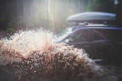 O carro 4wd offroad de Suv monta através da poça enlameada, estrada fora de estrada da trilha, com um respingo grande, durante um Fotografia de Stock Royalty Free