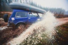 O carro 4wd offroad de Suv monta através da poça enlameada, estrada fora de estrada da trilha, com um respingo grande, durante um Fotos de Stock Royalty Free