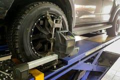 O carro 4WD submete-se à roda alinha na garagem Imagens de Stock Royalty Free