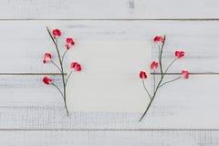 O cartão branco vazio decora com as flores de papel vermelhas Foto de Stock Royalty Free