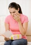 O cartão da leitura da mulher nova com presente envolveu o presente fotos de stock royalty free