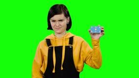 O cartão da menina em sua mão e mostra seu dedo para baixo Tela verde filme