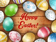 O cartão da Páscoa com cor eggs em um fundo de madeira Fotografia de Stock