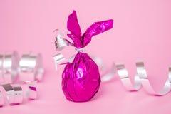 O cartão da Páscoa com doces coloriu as orelhas roxas do coelho do ovo no fundo serpentino cor-de-rosa Estilo mínimo, cores roxas fotos de stock