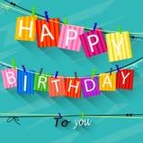 O cartão de aniversário com pregador de roupa e as letras coloridas penduram na corda Fotografia de Stock