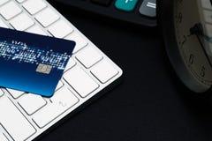 O cartão de crédito do close up no preto entra no botão, conceito da compra da conveniência foto de stock