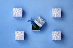 O cartão de memória Flash brilhante do usb do azul com uma curva azul encontra-se em uma caixa de presente pequena no azul com um Fotografia de Stock