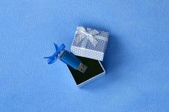 O cartão de memória Flash brilhante do usb do azul com uma curva azul encontra-se em uma caixa de presente pequena no azul com um Fotos de Stock