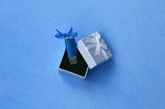 O cartão de memória Flash brilhante do usb do azul com uma curva azul encontra-se em uma caixa de presente pequena no azul com um Imagens de Stock Royalty Free