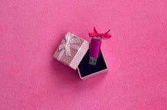 O cartão de memória Flash brilhante do usb do rosa com uma curva cor-de-rosa encontra-se em uma caixa de presente pequena no rosa Fotografia de Stock Royalty Free