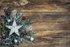O cartão de Natal com as quinquilharias brancas da estrela e do Natal no abeto ramifica foto de stock