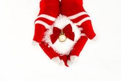 O cartão de Natal, luvas nas mãos que guardam a neve cronometra com tempo fi Imagem de Stock Royalty Free