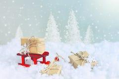 O cartão de Natal, trenó de madeira vermelho envolveu a caixa de presente Foto de Stock