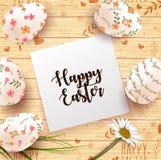 O cartão de Páscoa com ovos realísticos e a margarida florescem no fundo de madeira da textura
