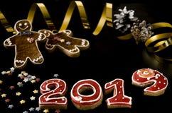 O cartão do ano novo nos números vermelhos 2019 com estrelas multi-coloridas, pão-de-espécie do pão-de-espécie preto do fundo equ imagens de stock royalty free