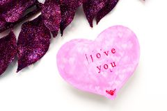 O cartão do dia de Valentim na forma de um coração cor-de-rosa com uma inscrição ama-o foto de stock royalty free