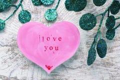 O cartão do dia de Valentim na forma de um coração cor-de-rosa com uma inscrição ama-o fotos de stock