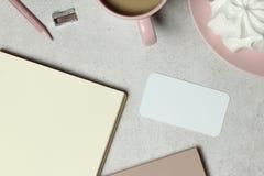O cartão do modelo com o papel do livro de nota, uma xícara de café cor-de-rosa, o lápis & o apontador imagens de stock royalty free