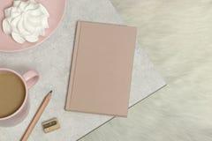 O cartão do modelo no granito com livro de nota, linhas cinzentas e cor-de-rosa, xícara de café e bolo, lápis, apontador, régua imagem de stock royalty free