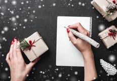 O cartão do Natal, uma senhora escreve-lhe desejos em um ambiente do xmas o ambiente do Natal é enchido com os flocos de neve Fotografia de Stock