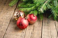 O cartão para os feriados do Natal enfeita o fundo de madeira do Natal do fundo dos brinquedos do Natal dos ramos Imagem de Stock Royalty Free